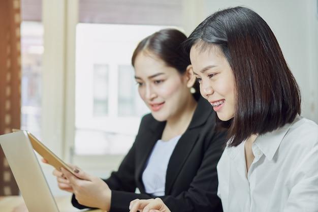 Zakelijke vrouwen gebruiken laptops en smartphones om op kantoor te werken. Premium Foto