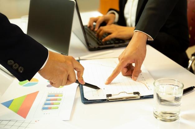 Zaken die financiële kwestingshanden bespreken met pen die op financiële grafiek richten. Premium Foto