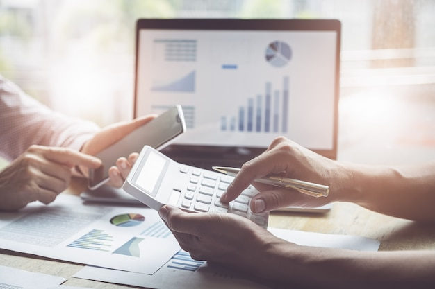 Zaken en vennootschap die gebruikend calculator bespreken om balans jaarlijks met holdingspen te herzien en laptop computer te gebruiken om begroting te berekenen. auditintegriteit voor investeringsconcept. Premium Foto