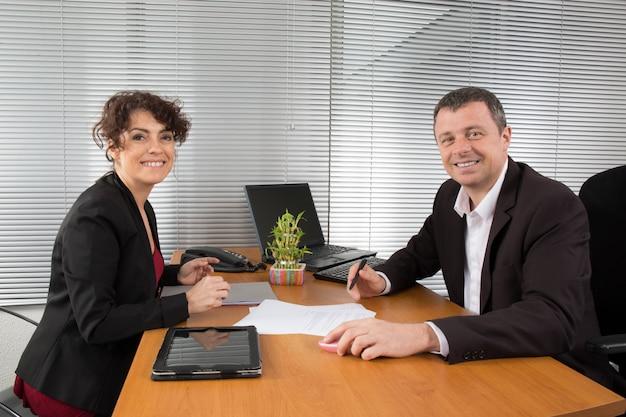 Zaken man en vrouw praten samen kijken naar document Premium Foto