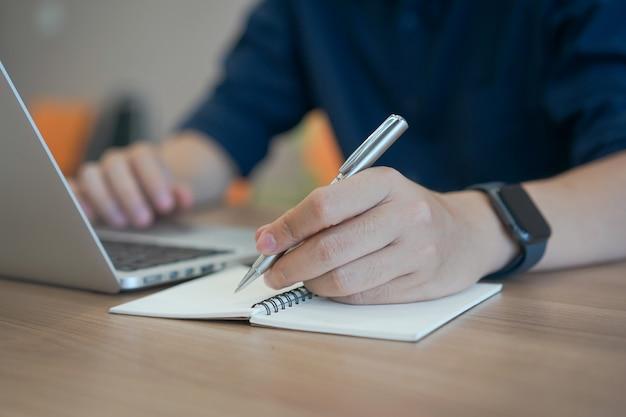 Zaken man hand schrijven inhoud of iets op laptop met behulp van laptop op kantoor thuis Premium Foto