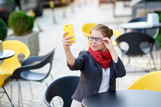 Zaken vrouw in glazen zitten aan een tafel in een café en maakt selfie Premium Foto