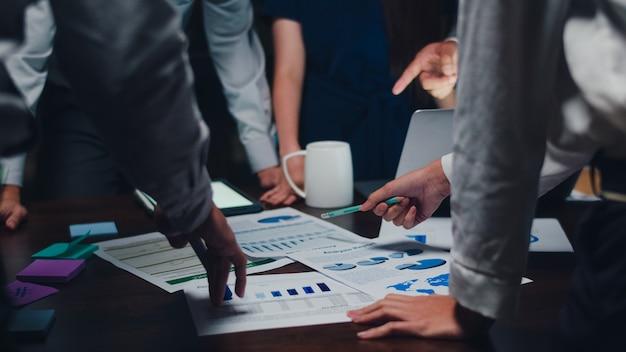 Zakenlieden en zakenvrouwen uit het millennial-azië ontmoeten brainstormingsideeën over nieuwe papierwerkprojectcollega's die samenwerken aan het plannen van een successtrategie. geniet van teamwork in een klein modern nachtkantoor. Gratis Foto