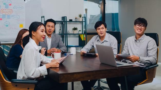 Zakenlieden en zakenvrouwen uit millennial azië die een videogesprek met een vergadering hebben, brainstormingsideeën hebben over nieuwe projectcollega's die samen een planningsstrategie ontwikkelen, genieten van teamwork in een modern kantoor. Gratis Foto