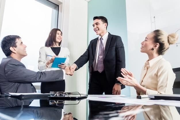 Zakenlieden schudden elkaar de hand na succesvolle deal Premium Foto