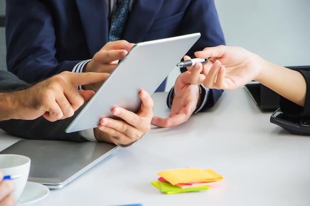 Zakenlieden zoeken en bekijken samen informatie op tablets om nieuwe projecten te creëren in de vergaderruimte op hun werkplek. Premium Foto