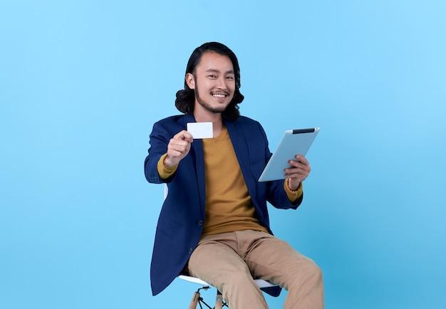 Zakenman aziatische gelukkig lachend creditcard tonen en met behulp van een digitale tablet zittend op een stoel op helderblauw. Gratis Foto