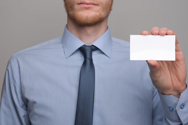 Zakenman, business man's hand houden visitekaartje tonen - close-up shot op grijze achtergrond. laat een blanco vel papier zien. papieren visitekaartje. Premium Foto