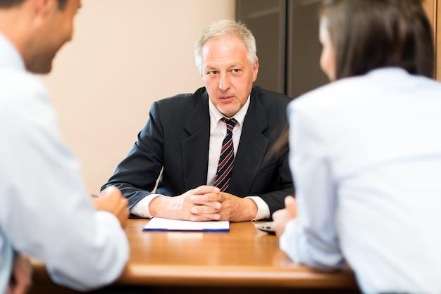 Zakenman die aan een paar in een bureau spreekt Premium Foto