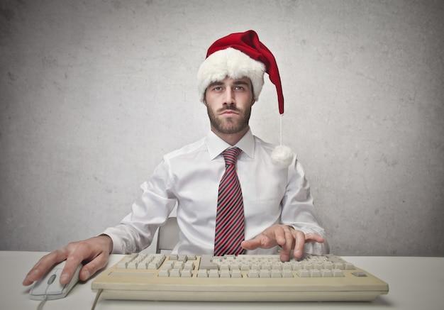 Zakenman die de hoed van de kerstman draagt Premium Foto