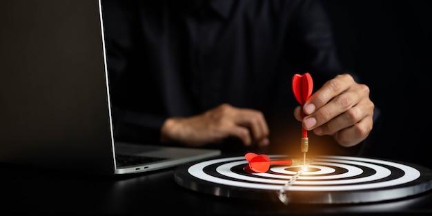 Zakenman die een pijltje houdt die gericht zijn op het bedrijfsdoel van het doelcentrum - Premium Foto
