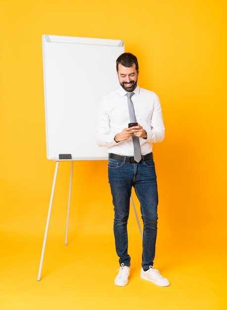 Zakenman die een presentatie geeft op wit bord een bericht verzendt met de mobiel Premium Foto