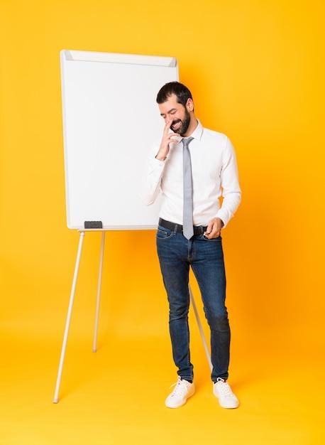 Zakenman die een presentatie op wit bord geeft die veel glimlacht Premium Foto