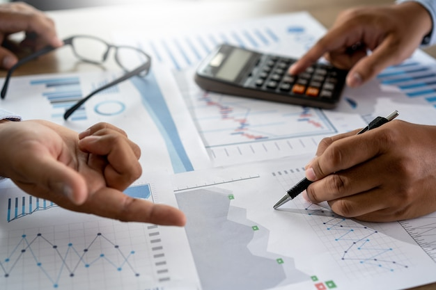 Zakenman die gebruikend een verwezenlijking van het de boekhoudingsconcept van calculatorfinanciën werken om mensen hulpboekhouding in evenwicht te brengen Premium Foto