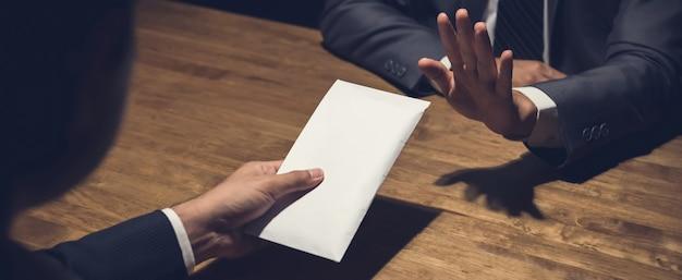 Zakenman die geld in witte envelop verwerpen die door zijn partner in het donkere, antiomkopingsconcept wordt aangeboden Premium Foto