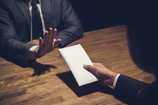 Zakenman die geld in witte envelop weigert die door zijn partner in dark wordt aangeboden Premium Foto