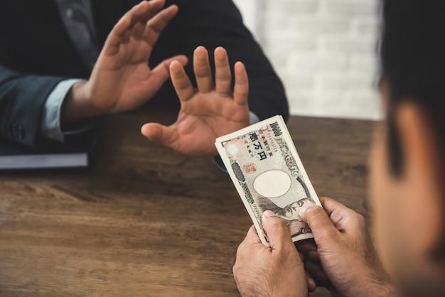 Zakenman die geld, japanse yenbankbiljetten weigert, die door zijn partner worden gegeven Premium Foto