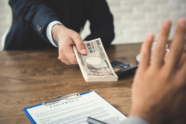 Zakenman die geld, japenese-yenbankbiljetten verwerpen, die door zijn partner worden aangeboden terwijl het maken van contract Premium Foto