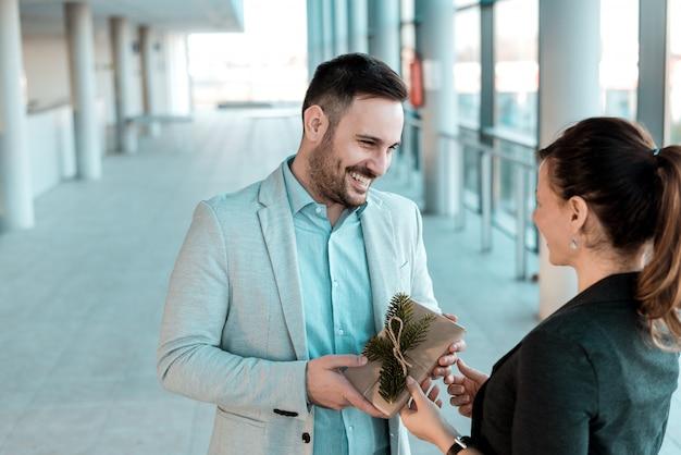 Zakenman die heden aan zijn vrouwelijke medewerker geeft. Premium Foto