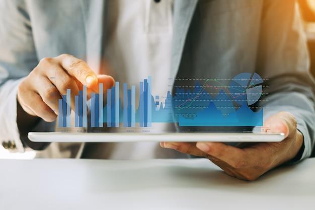 Zakenman die het saldo van het bedrijfs financiële rapport met digitale vergrote werkelijkheidsgrafiek analyseren. Premium Foto