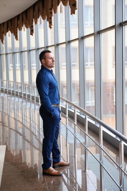 Zakenman die het venster in een reusachtig commercieel centrum bekijkt. Premium Foto