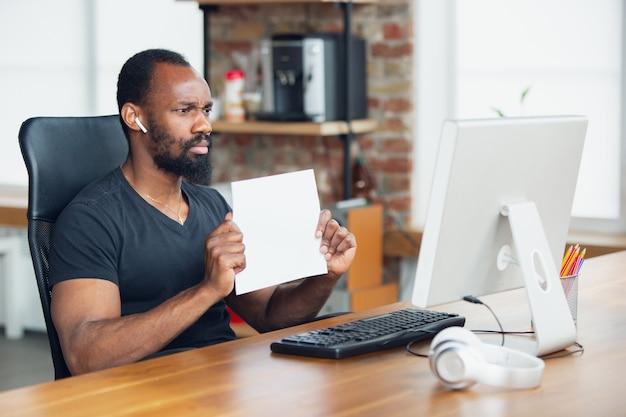 Zakenman die in bureau werkt en leeg aanplakbiljet houdt Gratis Foto