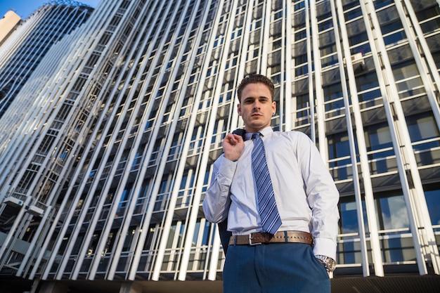 Zakenman die in elegant kostuum zijn jasje op achtergrond van moderne bureauwolkenkrabber houdt. Premium Foto