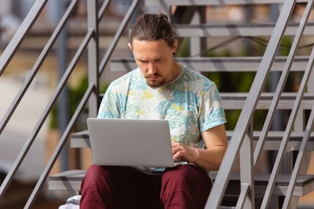 Zakenman die in openlucht met laptop werkt, die aan het computerscherm kijkt Gratis Foto
