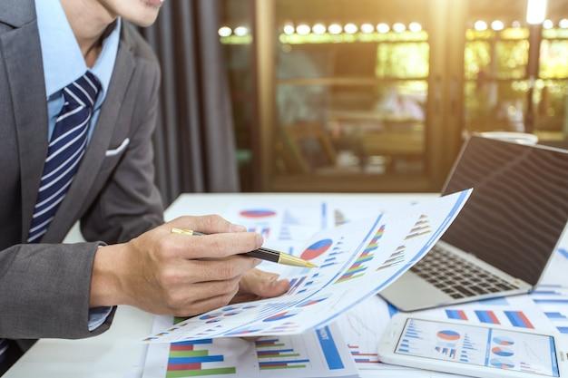 Zakenman die investeringsgrafieken analyseert. Premium Foto