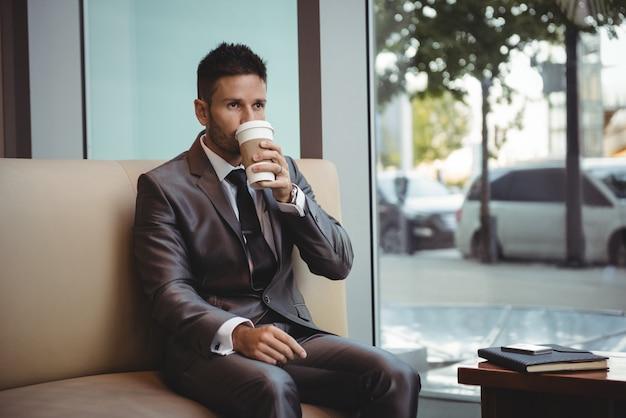 Zakenman die koffie heeft terwijl het zitten op bank Gratis Foto