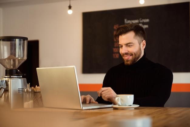 Zakenman die laptop met tablet op houten lijst in koffiewinkel met een kop van koffie met behulp van. Premium Foto