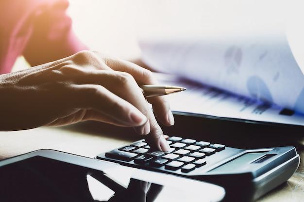 Zakenman die met calculator en digitale tablet met het financiële effect van de bedrijfsstrategielaag in bureau, boekhouder en controleursconcept werken. Premium Foto