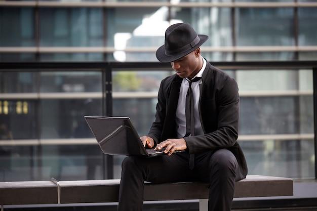 Zakenman die met mobiel en laptop in stedelijk milieu werkt Premium Foto