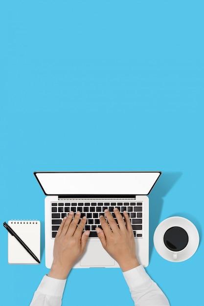 Zakenman die met moderne werkplaats met laptop aan blauwe lijst werkt, Premium Foto