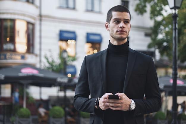 Zakenman die mobiele telefoon houdt en het in openlucht bekijkt Gratis Foto