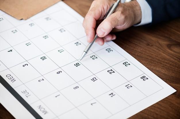 Zakenman die op kalender voor een benoeming merkt Gratis Foto