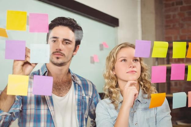 Zakenman die op papier schrijven terwijl vrouwen die in bureau lezen Premium Foto