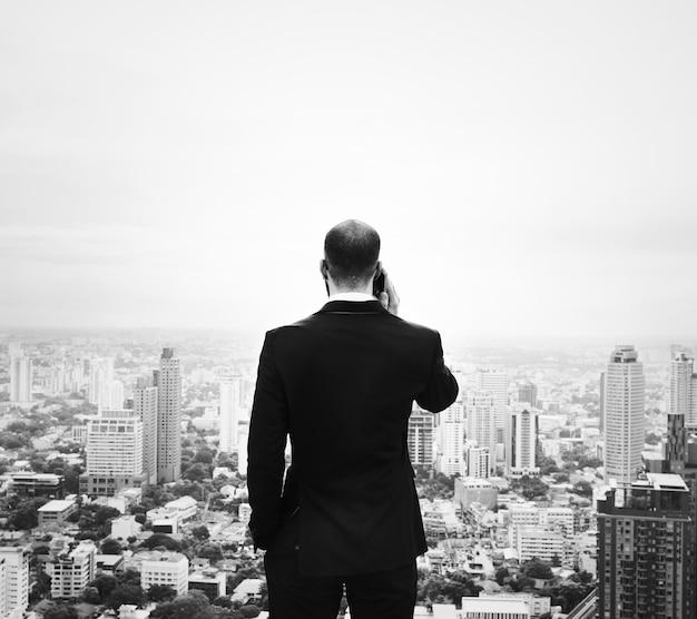 Zakenman die smartphone op de bovenkant van een gebouw gebruikt Gratis Foto
