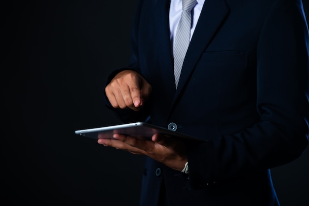 Zakenman die tablet gebruiken die verkoopgegevens en de economische grafiek van de de groeigrafiek, technologie analyseren Gratis Foto