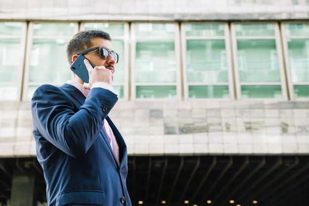 Zakenman die telefoongesprek in stedelijk milieu maakt Gratis Foto