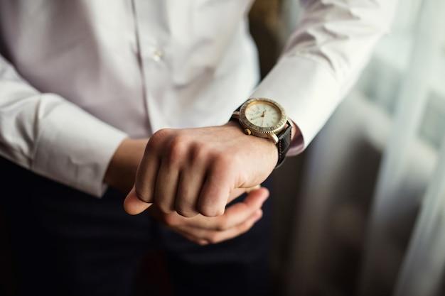 Zakenman die tijd op zijn polshorloge controleert, mens die klok bij de hand zet, bruidegom die klaar in de ochtend vóór huwelijksceremonie wordt Premium Foto