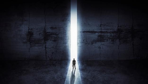 Zakenman die uit het abstracte openen in muur met helder daglicht kijkt Premium Foto