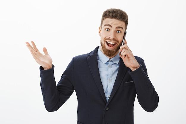 Zakenman die uitstekend nieuws ontvangt. blij en opgewonden opgetogen goed uitziende mannelijke ondernemer in elegant pak met smartphone in de buurt van oor praten, opgewekt hand opsteken en glimlachen van vreugde Gratis Foto
