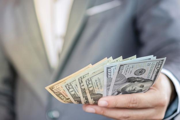 Zakenman die usd-bankbiljet voor betaling houden. amerikaanse dollar is de belangrijkste en meest populaire valuta in de wereld. investerings- en spaarconcept. Premium Foto