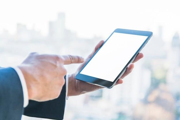Zakenman die vinger op digitale tablet met het lege scherm richt Gratis Foto