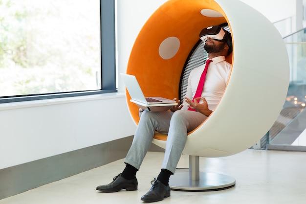 Zakenman die virtual reality-simulator gebruiken voor het mediteren Gratis Foto