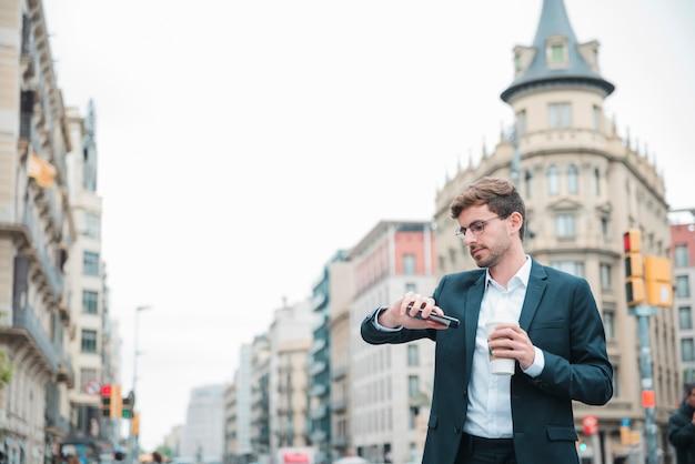 Zakenman die zich op stadsstraat het letten op tijd op zijn polshorloge bevindt Gratis Foto