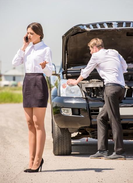 Zakenman die zijn gebroken auto probeert te herstellen. Premium Foto