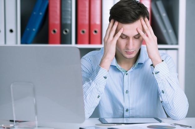 Zakenman die zijn hoofd ongerust houdt Premium Foto
