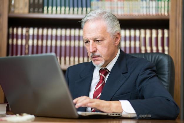 Zakenman die zijn laptop in een bibliotheek met behulp van Premium Foto